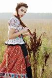 De jonge boervrouw, kleedde zich in Hongaars nationaal kostuum, dat over aardachtergrond stelt Stock Foto's