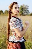 De jonge boervrouw, kleedde zich in Hongaars nationaal kostuum, dat over aardachtergrond stelt Stock Afbeeldingen
