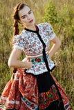 De jonge boervrouw, kleedde zich in Hongaars nationaal kostuum, dat over aardachtergrond stelt Stock Fotografie