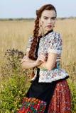 De jonge boervrouw, kleedde zich in Hongaars nationaal kostuum, dat over aardachtergrond stelt Royalty-vrije Stock Foto