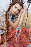 De jonge boervrouw, kleedde zich in Hongaars nationaal kostuum, dat over aardachtergrond stelt Royalty-vrije Stock Fotografie