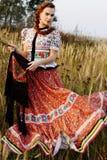 De jonge boervrouw, kleedde zich in Hongaars nationaal kostuum, dat over aardachtergrond stelt Royalty-vrije Stock Afbeelding