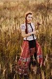 De jonge boervrouw, kleedde zich in Hongaars nationaal kostuum, dat over aardachtergrond stelt Stock Foto