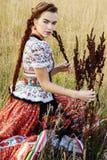 De jonge boervrouw, kleedde zich in Hongaars nationaal kostuum, dat over aardachtergrond stelt Stock Afbeelding