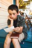 De jonge brief van de jongenslezing op voorportiek Royalty-vrije Stock Foto's