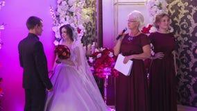 De jonge bruid en bruidegomtribune in huwelijkszaal en ceremoniemeester spreekt woorden op muur als achtergrond die met bloemen w stock video