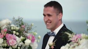 De jonge bruidegom bij de huwelijksceremonie bevindt zich bij het altaar van de boog en wacht op de bruid Huwelijk door het overz stock footage