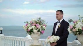 De jonge bruidegom bij de huwelijksceremonie bevindt zich bij het altaar van de boog en wacht op de bruid Huwelijk door het overz stock videobeelden