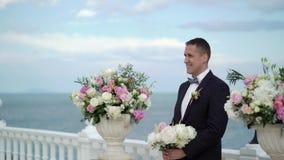 De jonge bruidegom bij de huwelijksceremonie bevindt zich bij het altaar van de boog en wacht op de bruid Huwelijk door het overz stock video