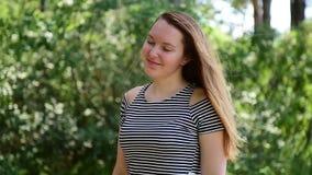 De jonge bruin-haired vrouw in gestreepte t-shirttribunes in het zonlicht tegen groen gebladerte, en de wind fladderen haar haar  stock footage
