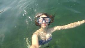 De jonge bruin-haired vrouw ligt op het water en onderwater met zwemmend masker zonder aqualong bij zonnige dag POV stock videobeelden