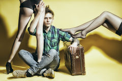 De jonge casanovamens met suitcasen amd vrouwelijke benen Royalty-vrije Stock Foto's