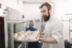 De jonge charismatische bakker zet een bakseldienblad met broodjes in de oven in de bakkerij royalty-vrije stock afbeeldingen