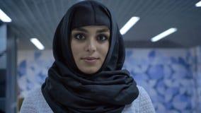 De jonge charmante moslimvrouw in hijab bevindt zich in onderdoorgang, lettend op bij camera, godsdienstconcept