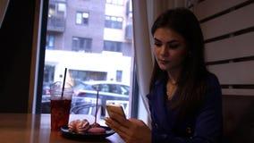 De jonge charmante vrouw drinkt een verfrissende drankzitting in een koffie stock footage
