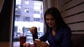 De jonge charmante vrouw drinkt een verfrissende drankzitting in een koffie stock videobeelden