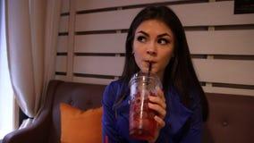 De jonge charmante vrouw drinkt een verfrissende drankzitting in een koffie stock video