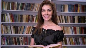 De jonge charmante vrouw leest boek, lettend op bij camera, het glimlachen, boekenrek op achtergrond stock videobeelden