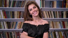 De jonge charmante vrouw let op bij camera, flirtconcept, boekenrek op achtergrond stock videobeelden