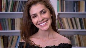 De jonge charmante vrouw let op bij camera, het glimlachen, flirtconcept, het dromen concept, boekenrek op achtergrond stock footage