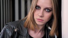 De jonge charmante vrouwen met zwaar maken omhoog in zwart jasje die op muur leunen en camera, gestreepte muurachtergrond onderzo stock video