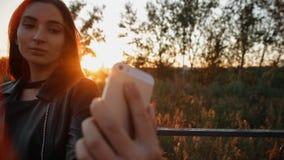 De jonge charmante vrouwenglazen maakt selfie lopend rond de stad bij zonsondergang stock videobeelden