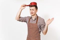 De jonge chef-kok of de kelner die van de pret gekke droevige mens in gestreepte bruine schort, overhemd rode lege die stewpan op stock foto's