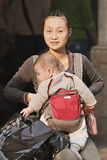 De jonge Chinese moeder met baby draagt binnen zak, Guanghzhou, China Stock Afbeeldingen