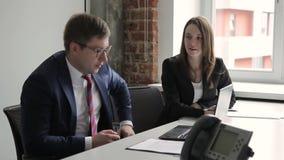 De jonge collega's spreken terwijl het zitten in belangrijk bedrijf stock videobeelden