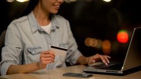 De jonge creditcard die van de vrouwenholding op laptop, online storting, transactie winkelen stock foto's