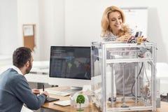 De jonge 3D printer van de vrouwenvestiging terwijl man die presentatie creëren Royalty-vrije Stock Afbeeldingen