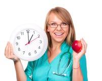 De jonge dame arts houdt klok die tonen Stock Foto