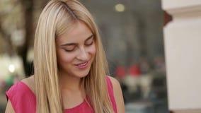 De jonge dame concentreerde zich in communicatie met haar vriend via digitale tablet op de straat stock videobeelden