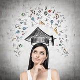 De jonge dame denkt over het bestuderen bij de universiteit De onderwijspictogrammen worden getrokken op concrete muur Stock Foto
