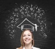 De jonge dame denkt over het bestuderen bij de universiteit De onderwijspictogrammen worden getrokken op het zwarte schoolbord Stock Foto