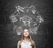 De jonge dame denkt over het bestuderen en graduatie De onderwijspictogrammen worden getrokken op het zwarte bord Stock Foto
