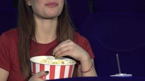 De jonge dame eet popcorn tijdens het onderzoek stock video