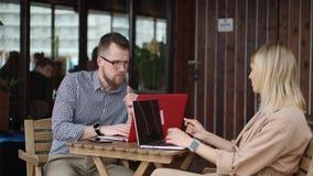 De jonge dame en de knappe kerel zitten bij lijst in open koffie, het werk met laptops stock footage