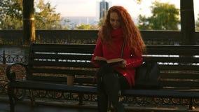 De jonge dame leest een boek, zit het rode hoofd mooie meisje op parkbank, de herfst de kleurrijke scène, lensgloed, ontspant stock footage
