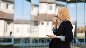 De jonge dame loopt met een kop van koffie langs de spiegelmuur buiten en typt iets in haar smartphone stock videobeelden