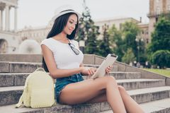 De jonge dame schrijft buiten bericht op haar pda terwijl op wandeling stock afbeeldingen