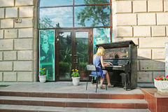 De jonge dame speelt in openlucht de piano op de dag van het Museum in Volgograd Stock Foto's