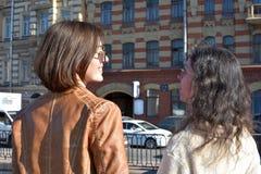 De jonge damestoeristen in Heilige Petersburg Rusland bevinden zich op een brug bij een geel van het gebouwenvierkant en horloge  stock fotografie