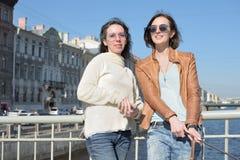 De jonge damestoeristen in Heilige Petersburg Rusland nemen selfies op een houten brug in het historische stadscentrum royalty-vrije stock afbeelding