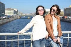 De jonge damestoeristen in Heilige Petersburg Rusland nemen selfies op een houten brug in het historische stadscentrum stock fotografie