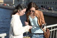 De jonge damestoeristen in Heilige Petersburg Rusland nemen selfies op een houten brug in het historische stadscentrum stock foto's