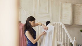 De jonge de kledingsontwerper en naaister naaien overhemd met draad en naald in kleermakersstudio stock video