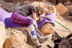 De jonge de reis van de vrouwen rustende leunende hond steen van de wandelingswoestijn Stock Foto