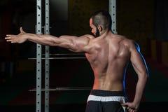 De jonge de Spierenbicepsen van de Bodybuilderverbuiging stellen Royalty-vrije Stock Afbeeldingen