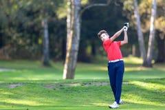 De jonge die golfspeler raakt een bestuurder van het T-stuk op een golf wordt geschoten cour stock afbeeldingen